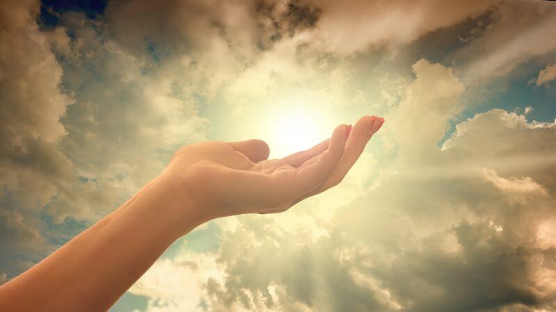 手を光にかざしている女性