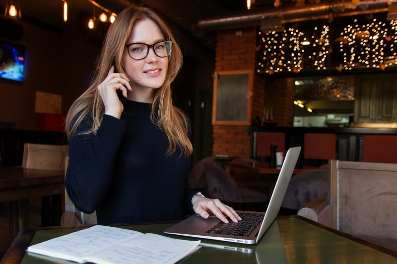 カフェで電話をしている女性